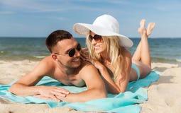 Happy couple in swimwear lying on summer beach Stock Photography