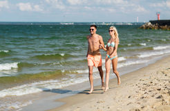 Happy couple in swimwear running on summer beach Royalty Free Stock Photos