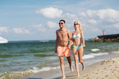 Happy couple in swimwear running on summer beach Royalty Free Stock Photo