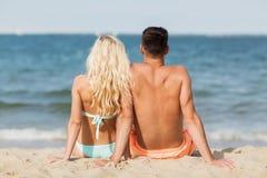 Happy couple in swimwear sitting on summer beach Royalty Free Stock Photos