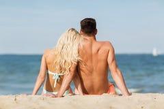 Happy couple in swimwear sitting on summer beach Stock Photos