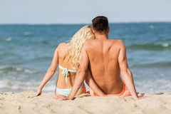 Happy couple in swimwear sitting on summer beach Stock Images