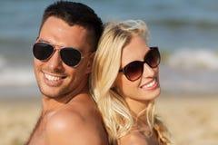 Happy couple in swimwear sitting on summer beach Stock Photo