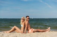 Happy couple in swimwear sitting on summer beach Stock Photography