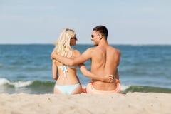 Happy couple in swimwear sitting on summer beach Royalty Free Stock Photo