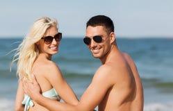 Happy couple in swimwear sitting on summer beach Stock Image