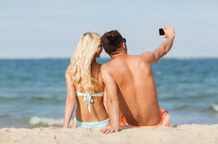 Happy couple in swimwear sitting on summer beach Royalty Free Stock Images