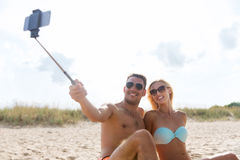 Happy couple in swimwear sitting on summer beach Royalty Free Stock Photography