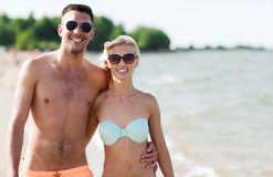 Happy couple in swimwear walking on summer beach Royalty Free Stock Photos