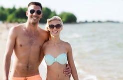 Happy couple in swimwear walking on summer beach Royalty Free Stock Photos