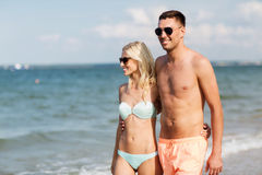 Happy couple in swimwear walking on summer beach Royalty Free Stock Photography