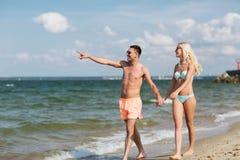 Happy couple in swimwear walking on summer beach Royalty Free Stock Image