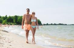 Happy couple in swimwear walking on summer beach Stock Photos