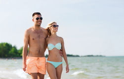 Happy couple in swimwear walking on summer beach Stock Image