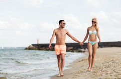 Happy couple in swimwear walking on summer beach Royalty Free Stock Image