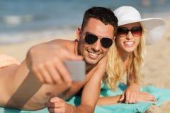 Happy couple in swimwear walking on summer beach Stock Images