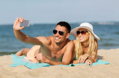 Happy couple in swimwear walking on summer beach Stock Image