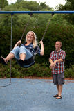 Happy Couple on swing set Royalty Free Stock Images