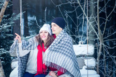 Happy couple on swing beside winter forest Stock Photography