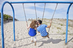 Happy couple on swings Stock Photos