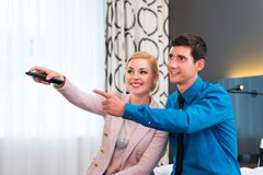 Couple switching TV with remote control in hotel room. Happy couple switching TV with remote control in hotel room royalty free stock image