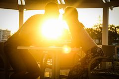 Happy couple at a table by the sea at sunset nature royalty free stock photos