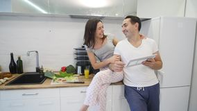 Happy couple with tablet computer in kitchen at home.  stock footage