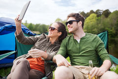 Happy couple with tablet pc at camping tent Stock Photo