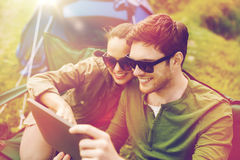 Happy couple with tablet pc at camping tent Royalty Free Stock Images