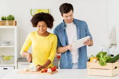 Happy couple with tablet pc cooking food at home Royalty Free Stock Photos