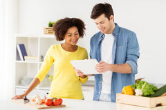 Happy couple with tablet pc cooking food at home Stock Photography