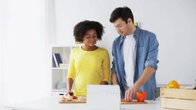 Happy couple with tablet pc cooking food at home stock video footage