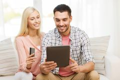 Happy couple with tablet pc and credit card. Technology, people, e-money and commerce concept - smiling happy couple with tablet pc computer and credit or bank Royalty Free Stock Photo