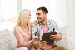 Happy couple with tablet pc and credit card Stock Photos
