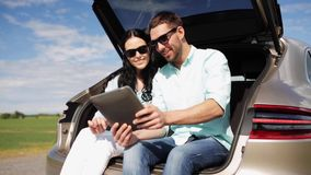 Happy couple with tablet pc at hatchback car trunk 34 stock video footage