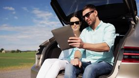 Happy couple with tablet pc at hatchback car trunk 25 stock footage