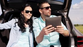 Happy couple with tablet pc at hatchback car trunk 35. Technology, travel, vacation, road trip and people concept - happy couple with tablet pc computer sitting stock footage