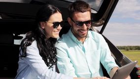 Happy couple with tablet pc at hatchback car trunk 33. Technology, travel, vacation, road trip and people concept - happy couple with tablet pc computer sitting stock video footage