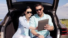 Happy couple with tablet pc at hatchback car trunk 37. Technology, travel, vacation, road trip and people concept - happy couple with tablet pc computer sitting stock video footage