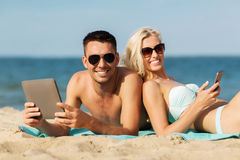 Happy couple with tablet pc sunbathing on beach Stock Photography