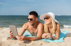 Happy couple with tablet pc sunbathing on beach Stock Images