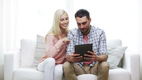 Happy couple with tablet pc viewing photos at home