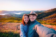 Happy couple takes selfie at beautiful Port Hills, Christchurch in New Zealand royalty free stock photography