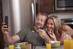 Happy couple takes selfie at breakfast. Happy loving couple eating breakfast takes a selfie royalty free stock image