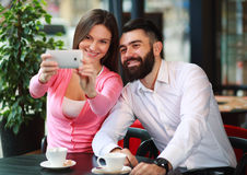 Happy couple taking photo with mobile phone in cafe Stock Image