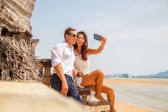 Happy couple taking a photo on white beach on honeymoon holiday. stock photography