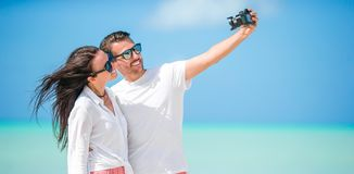 Happy couple taking a selfie photo on white beach. Two adults enjoying their vacation on tropical exotic beach Royalty Free Stock Images