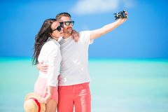 Happy couple taking a selfie photo on white beach. Two adults enjoying their vacation on tropical exotic beach Stock Image