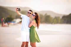 Happy couple taking a photo on white beach on honeymoon holidays. Happy couple taking a photo on white beach on honeymoon holiday Stock Photos