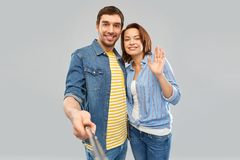 Happy couple taking picture by selfie stick. People concept - happy couple waving hand and taking picture by selfie stick over grey background stock photo